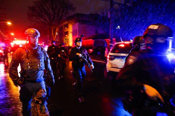 Law enforcement personnel walk near the scene following a shooting, Tuesday, Dec. 10, 2019, in Jersey City, N.J.  (AP Photo/Eduardo Munoz Alvarez)