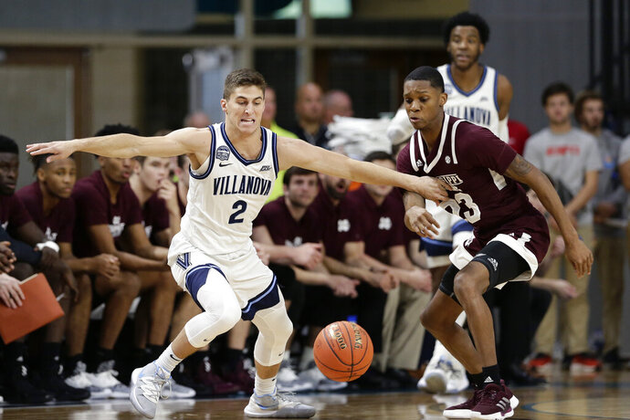 Villanova guard Collin Gillespie (2) and Mississippi State guard Tyson Carter (23) chase the ball during the first half of an NCAA college basketball game at the Myrtle Beach Invitational in Conway, S.C., Friday, Nov. 22, 2019. (AP Photo/Gerry Broome)