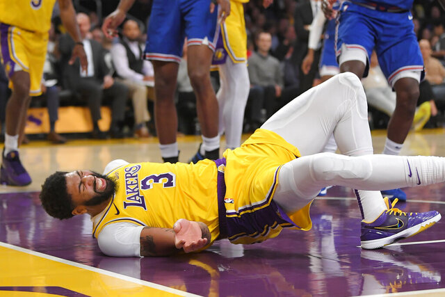 Los Angeles Lakers forward Anthony Davis winces as he hits the court after falling while trying to defend against a shot by New York Knicks forward Julius Randle during the second half of an NBA basketball game Tuesday, Jan. 7, 2020, in Los Angeles. Davis left the game. The Lakers won 117-87. (AP Photo/Mark J. Terrill)