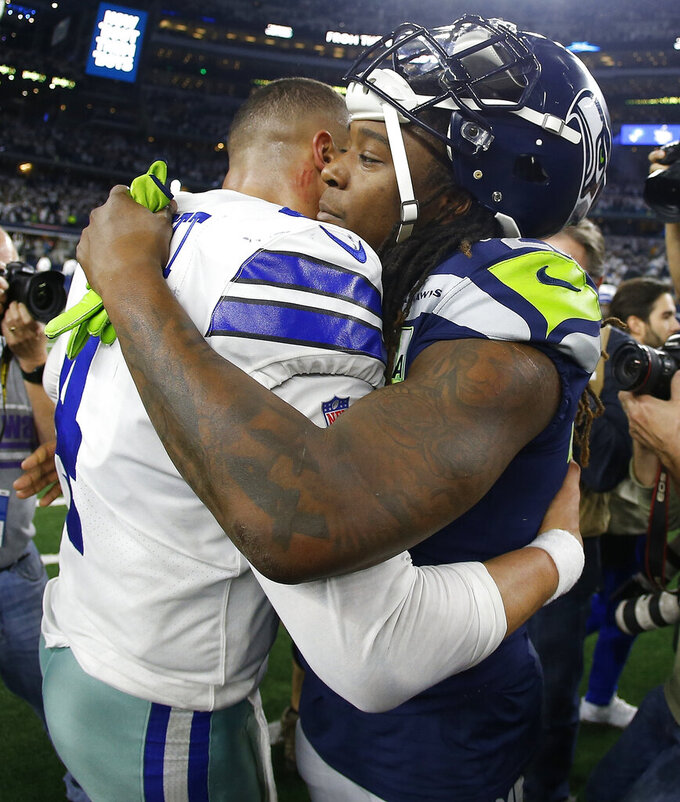 Dallas Cowboys quarterback Dak Prescott (4) and Seattle Seahawks cornerback Shaquill Griffin (26) embrace after the NFC wild-card NFL football game in Arlington, Texas, Saturday, Jan. 5, 2019. The Cowboys won 24-22. (AP Photo/Ron Jenkins)