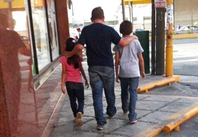 BEST QUALITY AVAILABLE - This July 24, 2019 photo courtesy of Guatemalan migrant Lucia shows her husband Rene with their 7-year-old daughter and 11-year-old son, as they walk in search of a place to sleep in Monterrey, Mexico. Rene said they were given a Sept. 20 court date in the U.S. for their asylum request, and promised Mexico would provide housing, work and schooling, but in Mexico they were bused to Monterrey without explanation or support. (Lucia via AP)