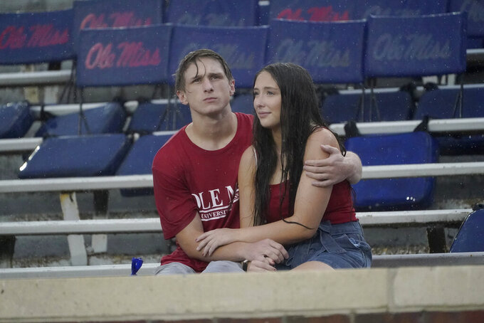Mississippi coeds sit in the rain prior to an NCAA college football game against Tulane, Saturday, Sept. 18, 2021, in Oxford, Miss. A weather delay was called by officials. (AP Photo/Rogelio V. Solis)