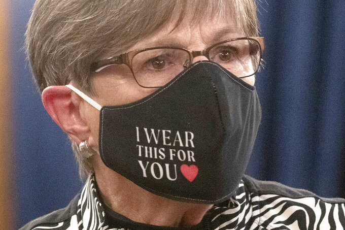 FILE - In this July 2020, file photo, Kansas Gov. Laura Kelly wears a protective mask during a news conference in Topeka. Johnson County District Judge David Hauber, in Kansas' most populous county, has struck down as unconstitutional a state law requiring unusually speedy legal hearings for people challenging mask requirements and other COVID restrictions. (Evert Nelson/The Topeka Capital-Journal via AP, File)