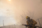 A firefighter carries a hose during work to protect homes from the flames of a wildfire in the Pacific Palisades area of Los Angeles, Monday, Oct. 21, 2019. (AP Photo/Christian Monterrosa)