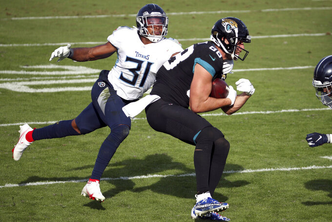 Jacksonville Jaguars tight end Tyler Eifert, right, makes a reception for an 18-yard gain in front of Tennessee Titans safety Kevin Byard (31) during the second half of an NFL football game, Sunday, Dec. 13, 2020, in Jacksonville, Fla. (AP Photo/Stephen B. Morton)