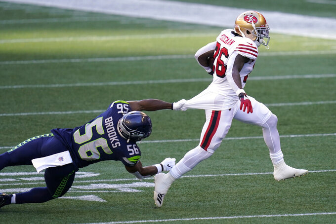 Seattle Seahawks linebacker Jordyn Brooks (56) grabs the jersey of San Francisco 49ers running back Tevin Coleman, right, during the first half of an NFL football game, Sunday, Nov. 1, 2020, in Seattle. (AP Photo/Elaine Thompson)