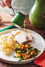 In this May 2019 photo gravy is poured on a plate of turkey, mash potatoes and gravy and a side of sauteed broccoli rabe, corn and onions with crispy bacon, on a table in New York. If you remember that the turkey breast will take less time to cook than the legs, and that you can get a head start on your gravy, Thanksgiving will be a whole lot less stressful. (Cheyenne Cohen/Katie Workman via AP)