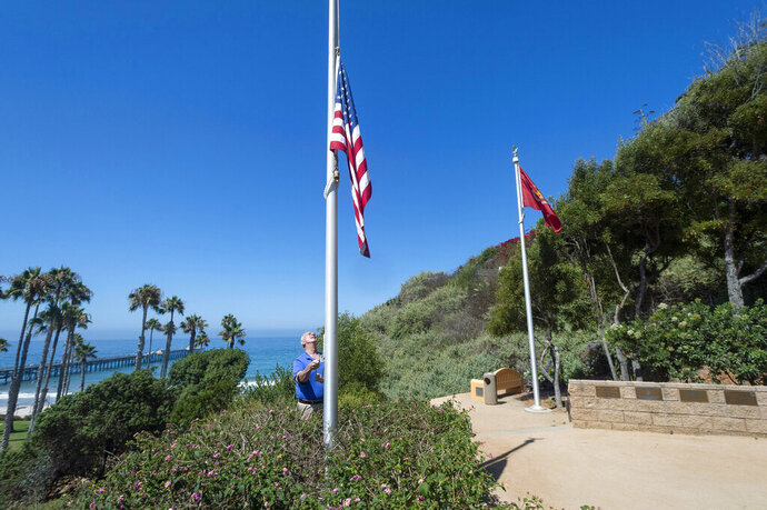 Former San Clemente Mayor Wayne Eggleston lowers the U.S. flag to half-staff at Park Semper Fi in San Clemente, Calif., on Friday, July 31, 2020. Officials say a military seafaring assault vehicle with 15 Marines and a Navy sailor aboard sank off the coast of Southern California. A Marine Corps spokesman says they were traveling in the amphibious assault vehicle from the shores of San Clemente Island to a Navy ship Thursday evening when they reported that the vehicle was taking on water. (Paul Bersebach/The Orange County Register via AP)
