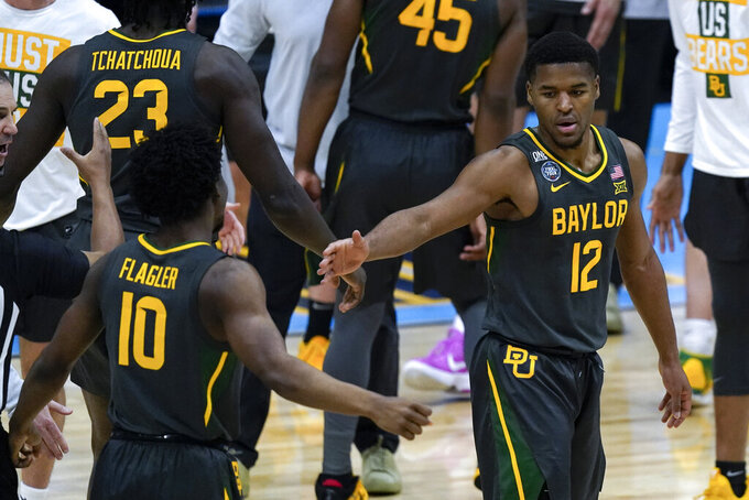 Baylor guard Jared Butler (12) celebrates with teammate guard Adam Flagler (10) during a timeout in the first half of the championship game against Gonzaga in the men's Final Four NCAA college basketball tournament, Monday, April 5, 2021, at Lucas Oil Stadium in Indianapolis. (AP Photo/Michael Conroy)