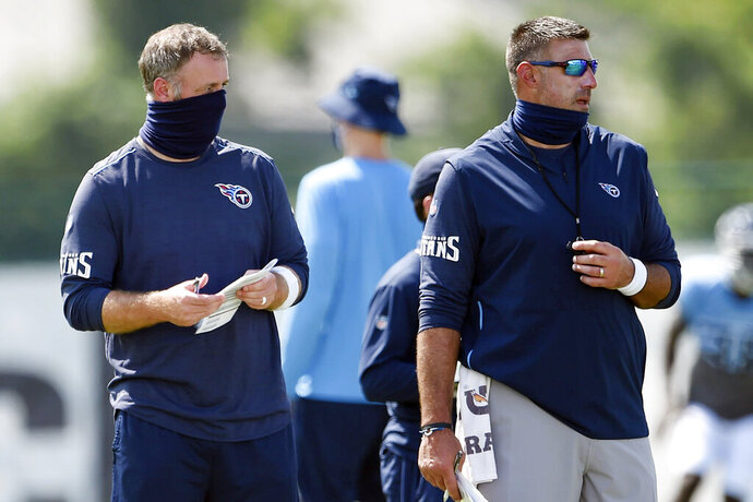 """FILE - In this Aug. 24, 2020, file photo, Tennessee Titans outside linebackers coach Shane Bowen, left, and head coach Mike Vrabel watch players during NFL football training camp in Nashville, Tenn. The NFL and the NFL Players Association found instances when the Titans failed to wear masks at all times and were """"insufficiently clear"""" to players about not meeting or working out once the facility closed in a review given to the team Monday, Oct. 19, 2020, a person familiar with the investigation told The Associated Press.But the person familiar with the review says there was no discussion of any discipline for an individual including general manager Jon Robinson, coach Mike Vrabel or any players, and there was no discussion of punishment, including forfeitures or draft picks. (George Walker IV/The Tennessean via AP, Pool, File)"""