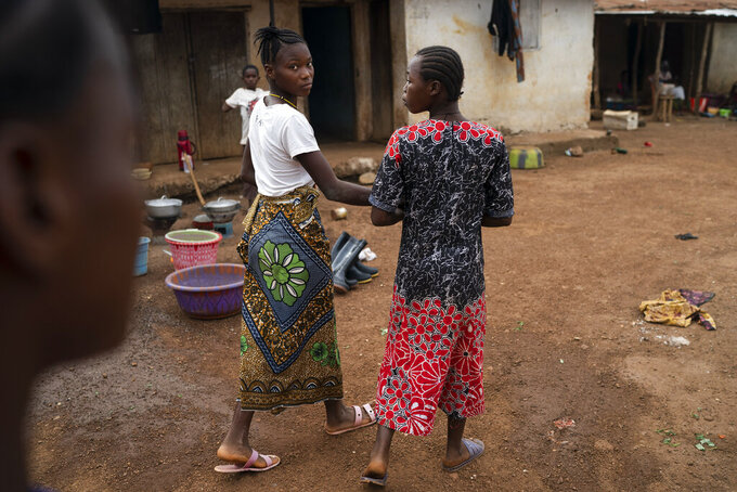 """Marie walks with a friend on a street in Komao village, on the outskirts of Koidu, district of Kono, Sierra Leone, Sunday, Nov. 22, 2020. A man, in his mid-20s, first caught a glimpse of Marie as she ran with her friends past his house near the village primary school. Soon after, he proposed to the fifth-grader. """"I'm going to school now. I don't want to get married and stay in the house,"""" she told him. But the pressures of a global pandemic on this remote corner of Sierra Leone were greater than the wishes of a schoolgirl. (AP Photo/Leo Correa)"""
