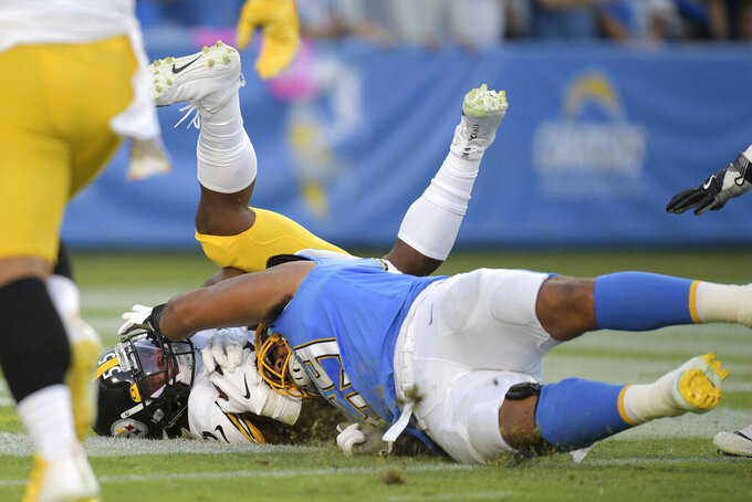 Pittsburgh Steelers linebacker Devin Bush, left, dives in for a touchdown past Los Angeles Chargers offensive tackle Sam Tevi after picking up a backward pass by Chargers quarterback Philip Rivers during the first half of an NFL football game, Sunday, Oct. 13, 2019, in Carson, Calif. (AP Photo/Kyusung Gong)