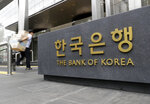 A man carrying boxes walk by the sign of the Bank of Korea in Seoul, South Korea, Thursday, July 12, 2018. South Korea's central bank has cut its forecast on the country's economy, citing mounting uncertainties from the U.S.-China trade battle. Bank of Korea said Thursday it lowered its growth outlook on Asia's fourth-largest economy to 2.9 percent this year, compared with its earlier forecast of 3 percent growth.(AP Photo/Lee Jin-man)