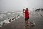 Cheri Daigle, a retired teache, takes a photo as Tropical Storm Nicholas approaches the Texas coast Monday, Sept. 13, 2021, along the seawall in Galveston, Texas. (Jon Shapley/Houston Chronicle via AP)