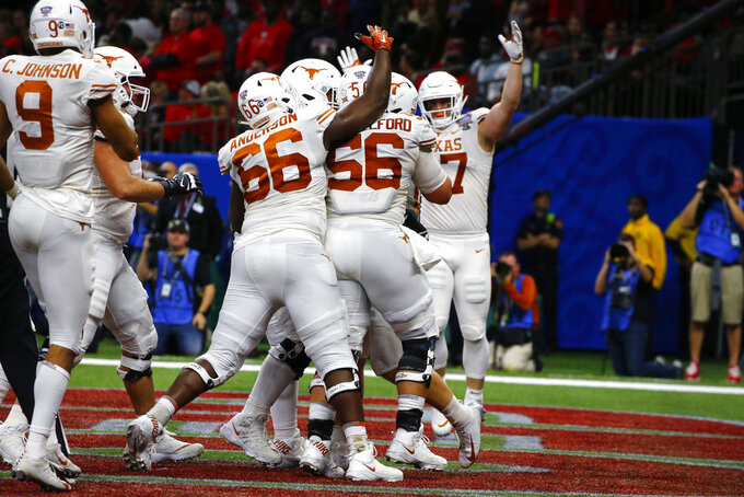 Texas players celebrate a touchdown carry by quarterback Sam Ehlinger, obscured, during the first half of the Sugar Bowl NCAA college football game against Georgia in New Orleans, Tuesday, Jan. 1, 2019. (AP Photo/Butch Dill)
