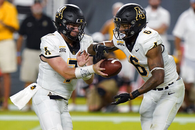 Appalachian State quarterback Chase Brice (7) hands off to running back Camerun Peoples (6) during the first half of an NCAA college football game against Miami, Saturday, Sept. 11, 2021, in Miami Gardens, Fla. (AP Photo/Wilfredo Lee)