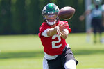 New York Jets quarterback Zach Wilson looks one way while tossing the ball the opposite way during NFL football practice on Thursday, May 27, 2021, in Florham Park, N.J. (AP Photo/Kathy Willens)