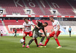Karim Onisiwo, center, of FSV Mainz 05 is challenged by Cologne's Noah Katterbach during the German Bundesliga soccer match between 1. FC Cologne and FSV Mainz 05 in Cologne, Germany, Sunday, May 17, 2020. The German Bundesliga becomes the world's first major soccer league to resume after a two-month suspension because of the coronavirus pandemic. (AP Photo/Lars Baron, Pool)