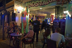 Police officers talk with the owner of a bar as people sit at the terrace in Fuengirola, near Malaga, Spain, Saturday, Aug. 8, 2020. The increase in Spain of coronavirus outbreaks associated with nightlife has set off alarms in recent days, mainly in tourist areas where pubs and discos are full before the summer tourist campaign. (AP Photo/Jesus Merida)