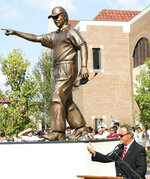 FILE - In this Sept. 24, 2004, file photo, Florida State head coach Bobby Bowden, lower right, speaks to the crowd following the unveiling of a statue in his likeness in front of the Florida State athletic department in Tallahassee, Fla. Bowden, the folksy Hall of Fame coach who built Florida State into an unprecedented college football dynasty, has died. He was 91. Bobby's son, Terry, confirmed to The Associated Press that his father died at home in Tallahassee, Fla., surrounded by family early Sunday, Aug. 8, 2021. (AP Photo/Phil Coale, File)