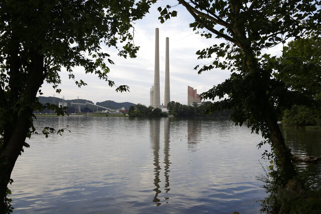 FILE  - In this Aug. 7, 2019, photo, the Kingston Fossil Plant stands near a waterway in Kingston, Tenn. The Trump administration will let some leaking or otherwise dangerous coal ash storage ponds stay in operation for years more and some unlined ponds stay open indefinitely under a rule change announced Friday, Oct. 16, 2020.  In 2008, the six-story-tall dike on a massive coal ash pond at the Tennessee plant collapsed, releasing more than a billion gallons of coal ash into the Swan Pond community. It remains the largest industrial spill in modern U.S. history and prompted the 2015 regulations that were intended to increase oversight of the industry. (AP Photo/Mark Humphrey, File)