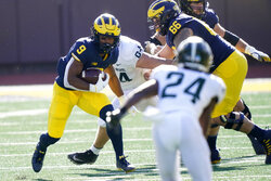 Michigan running back Chris Evans (9) looks for a hole during the first half of an NCAA college football game against Michigan State, Saturday, Oct. 31, 2020, in Ann Arbor, Mich. (AP Photo/Carlos Osorio)
