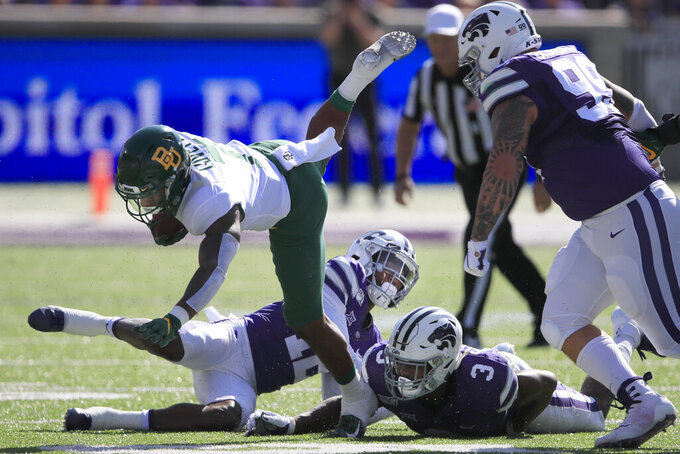 Baylor running back John Lovett (7) is tripped up by Kansas State defensive back AJ Parker (12) and linebacker Elijah Sullivan (3)during the first half of an NCAA college football game in Manhattan, Kan., Saturday, Oct. 5, 2019. Kansas State defensive tackle Trey Dishon (99) follows the play. (AP Photo/Orlin Wagner)