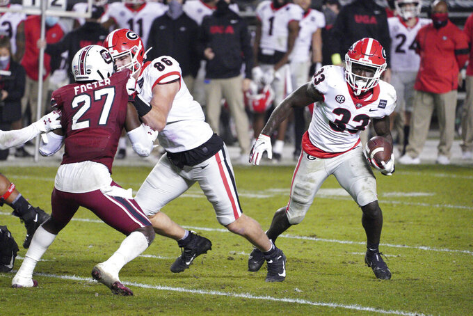 Georgia running back Daijun Edwards (33) carries the ball behind a block from John FitzPatrick (86) against South Carolina defensive back Jaylan Foster (27) during the second half of an NCAA college football game Saturday, Nov. 28, 2020, in Columbia, S.C. (AP Photo/Sean Rayford)