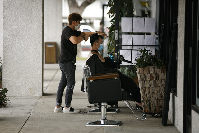 Hairstylist Travis Vu gives a haircut to Minh Dao at his outdoor hair salon in Fountain Valley, Calif., Wednesday, July 22, 2020.  The worsening COVID pandemic risks choking off the U.S. economy's fragile recovery and turn what some investors hoped would be a sprint back to normal into a long hard slog. States like California that had begun to take tentative steps to reopen are reversing course, while states across the Sunbelt that balked at taking preventative measures in the Spring are quickly backtracking as the number of Americans hospitalized or dying from the virus hits new records. (AP Photo/Jae C. Hong)