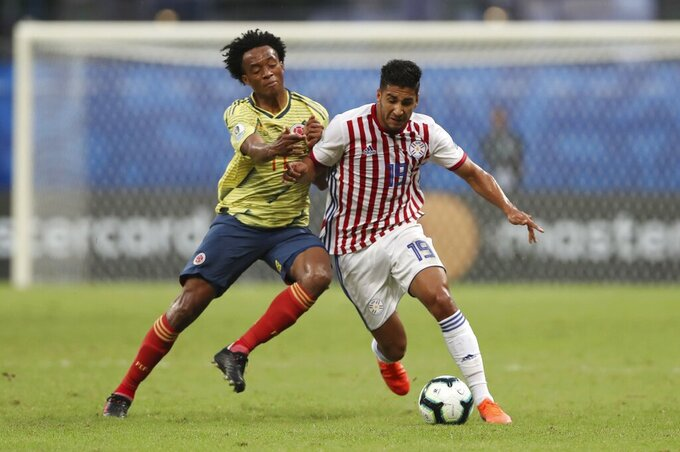 FILE - Colombia's Juan Cuadrado, left, battles for the ball with Paraguay's Cecilio Dominguez during a Copa America Group B soccer match at the Arena Fonte Nova in Salvador, Brazil, in this Sunday, June 23, 2019, file photo. Forward Cecilio Dominguez signed as Austin FC's first DP last summer after the Paraguayan international made his move from Independiente in Argentina. (AP Photo/Ricardo Mazalan, File)