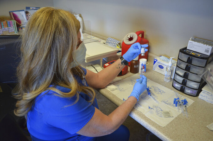 Southwest Utah Public Health Department supervisor Robin McMullin fills up syringes with the Moderna vaccine on Jan. 11, 2021, in Panguitch, Utah. The coronavirus pandemic has swept through this part of rural Utah, infecting more than one in every dozen people. (Lexi Peery/KUER, via AP)