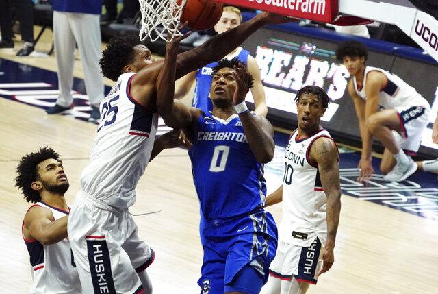 Connecticut forward Josh Carlton (25) fouls Creighton guard Antwann Jones (0) in the first half of an NCAA college basketball game in Storrs, Conn., Sunday, Dec. 20, 2020. (David Butler II/Pool Photo via AP)