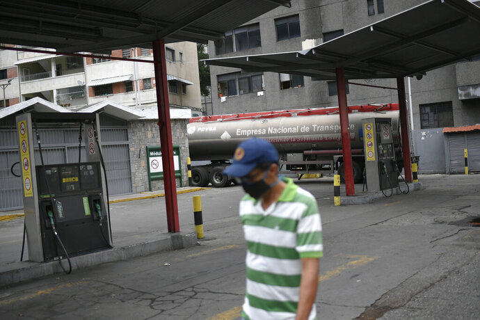 A man wearing a face mask amid the new coronavirus pandemic walks in front of an empty state oil company gas station while a tanker truck unloads gasoline in Caracas, Venezuela, Sunday, May 31, 2020. After decades of being the cheapest gasoline in the world, Venezuelan President Nicolas Maduro indicates that as of next Monday a new pricing scheme will be imposed on some 200 stations. (AP Photo/Matias Delacroix)