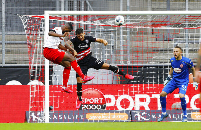 FC Cologne's Anthony Modeste scores their first goal during a German Bundesliga soccer match between 1. FC Cologne and Fortuna Duesseldorf in Cologne, Germany, Sunday, May 24, 2020.  (Thilo Schmuelgen/pool via AP)