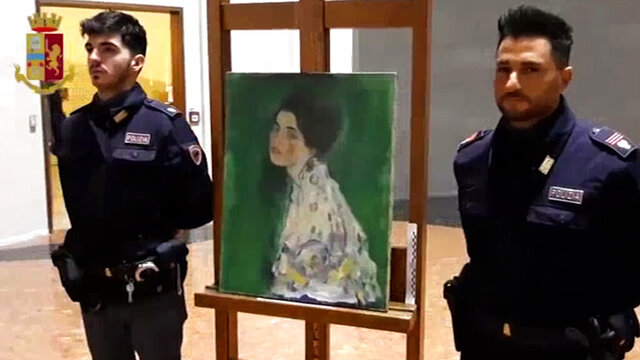 """This image taken from a video distributed Wednesday, Dec. 11, 2019 by Italian police shows two police officers standing next to painting which was found inside a gallery's walls, in Piacenza, northern Italy. A gardener at the Ricci Oddi modern art gallery in the northern city of Piacenza told Italian state TV on Tuesday that he was clearing ivy from the gallery's walls when he noticed a metal panel in which he found a bag inside a space within the walls. When the bag was opened it contained a painting that might be Klimt's """"Portrait of a Lady,"""" which disappeared from the gallery during renovations in February 1997. (Italian Police via AP)"""
