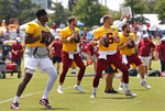 Washington Redskins quarterbacks, left to right,, Dwayne Haskins Jr. (7) Colt McCoy (12) Josh Woodrum (6) and Case Keenum (8) run drills during NFL football training camp, Tuesday, Aug. 6, 2019 in Richmond, Va. (Mark Gormus/Richmond Times-Dispatch via AP)