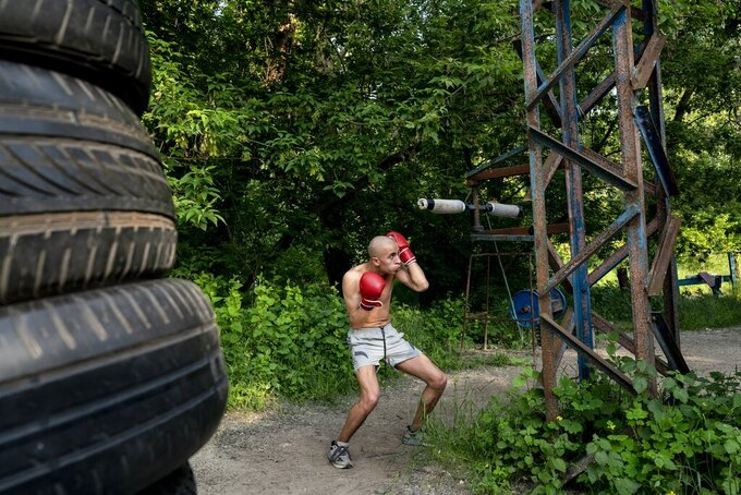 In this photo taken on Saturday, June 6, 2020, a man trains to box in the outdoors gym on the Dolobetskiy island on the Dnipro River in Kyiv, Ukraine. Relishing an opportunity to do exercise after a long lockdown, hundreds of Kyiv residents flock to an improvised outdoor workout on an island facing the Ukrainian capital. The Kachalka gym on the Dolobetskiy island on the Dnipro river has enjoyed broad popularity ever since it opened in 1966. (AP Photo/Evgeniy Maloletka)