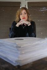In this Tuesday, Jan. 7, 2020, photo, Amy Braley Franck, a civilian victim advocate with the 416th Theater Engineer Command, poses for a portrait with more than 800 pages from several sexual abuse reports at her home in Oswego, Ill. Leaders of the U.S. Army Reserve unit that controls thousands of soldiers across the western United States have mishandled at least two sexual assault complaints by not properly referring them for outside investigation, according to victims, their advocate and documents obtained by The Associated Press. (AP Photo/Charles Rex Arbogast)