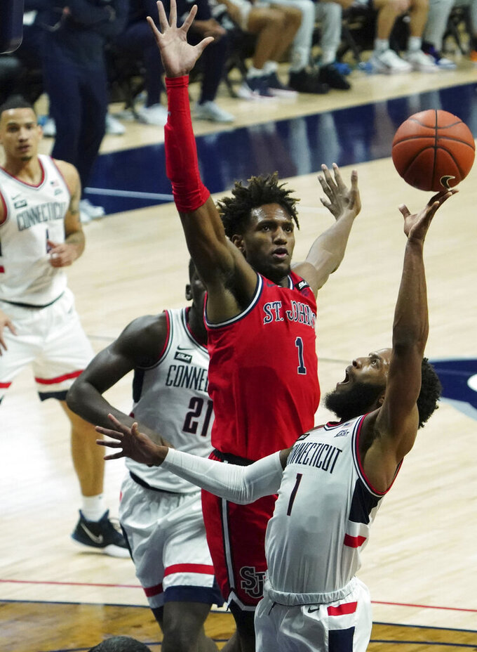 UConn guard R.J. Cole shoots as St. John's forward Josh Roberts (1) defends, in the first half of an NCAA college basketball game in Storrs, Connecticut, Monday, Jan. 18, 2021.  (David Butler II/Pool photo via AP)