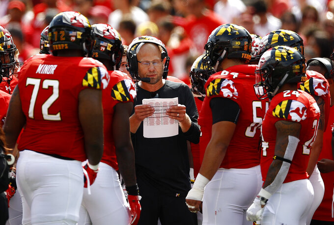 FILE - In this Saturday, Sept. 22, 2018, file photo, Maryland interim head coach Matt Canada, center, huddles with players in the first half of an NCAA college football game against Minnesota,, in College Park, Md. Playing the dual role of interim coach and offensive coordinator, Canada has kept the Terrapins (3-2, 1-1) in contention for a bowl bid during a season dedicated to fallen teammate Jordan McNair.  (AP Photo/Patrick Semansky, File)