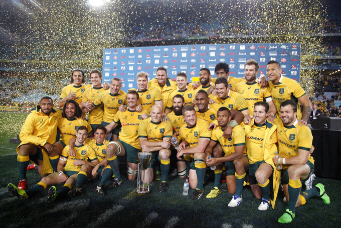 FILE - In this Aug. 8, 2015, file photo, the Australian team poses for a photo with their trophy after defeating New Zealand in their Rugby Championship match in Sydney. Rugby Australia says Tuesday, June 2, 2020, it wants to establish a quarantine hub which will enable it to host the Rugby Championship if the tournament is staged during the carryover effects of the coronavirus pandemic. (AP Photo/Rick Rycroft, File)