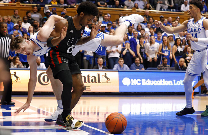 Duke forward Matthew Hurt falls out-of-bounds while chasing the ball with Miami guard Chris Lykes (0) during the first half of an NCAA college basketball game in Durham, N.C., Tuesday, Jan. 21, 2020. (AP Photo/Gerry Broome)