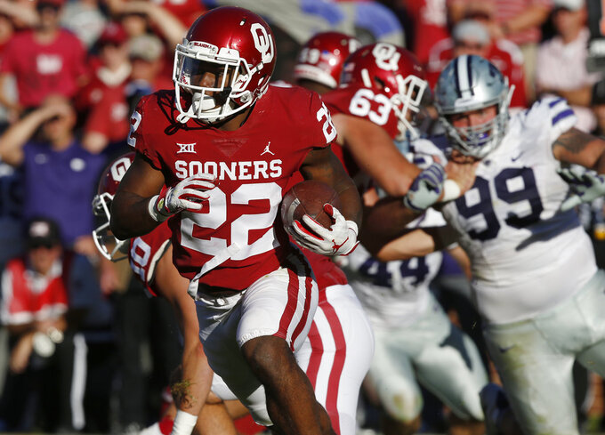 Oklahoma running back T.J. Pledger (22) carries the ball in the second half of an NCAA college football game against Kansas State in Norman, Okla., Saturday, Oct. 27, 2018. (AP Photo/Sue Ogrocki)