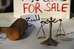 FILE - In this Dec. 3, 2020 file photo, Lebanese activists display symbols of justice during a protest against the slow pace of the investigation into the August 4 explosion that hit Beirut's seaport, outside the Justice Palace, in Beirut. A public feud in recent weeks among prosecutors has starkly demonstrated how Lebanon's system of sectarian factions is paralyzing Lebanon's judicial system and snarling attempts to root out corruption. (AP Photo/Hussein Malla, File)