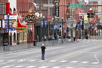 A man stands in the middle of Broadway to take a picture, where the streets and sidewalks are normally filled Monday, March 23, 2020, in Nashville, Tenn. More cities and counties in Tennessee have issued strict orders for nonessential businesses to shut down temporarily and people to stay at home as much as possible to curb the spread of the coronavirus. (AP Photo/Mark Humphrey)