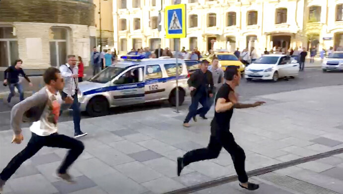 In this image taken from video provided by Viktoria Geranovich, a taxi driver, right, runs away from the scene after he crashed his taxi into pedestrians on a sidewalk near Red Square in Moscow, Russia, Saturday, June 16, 2018. Eight people, including two from Mexico, were injured in the crash. Video circulated on Russian social media and some news websites showed the taxi approaching a stopped line of cars, then veering onto the sidewalk and striking pedestrians. It then hit a traffic sign and bystanders tried to wrestle the driver out of the taxi, but he broke their grip and ran away; it was not clear how he was finally detained. (Viktoria Geranovich via AP)