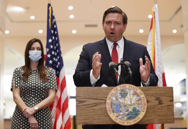 Florida Gov. Ron DeSantis gestures as he speaks during a news conference along side Lt. Gov. Jeanette Nunez, Tuesday, May 26, 2020, at the Miami-Dade Public Library in Miami. DeSantis appointed two South Floridians to the state Supreme Court on Tuesday: a Palm Beach County circuit judge who immigrated from Jamaica and, a former assistant U.S. attorney who is the son of Cuban immigrants. (AP Photo/Wilfredo Lee)
