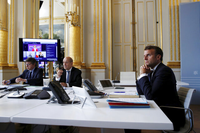 French President Emmanuel Macron, right, listens as he attends with French Foreign Minister Jean-Yves le Drian, center, an international videoconference on vaccination at the Elysee Palace in Paris, Monday, May 4, 2020. An alliance of world leaders is hoping a virtual summit could lead to billions of dollars to fund research into a vaccine for the new coronavirus as well as develop better treatments and more efficient testing. The leaders of France, Germany, Italy and Norway and top European Union officials said the money raised will be channeled mostly through recognized global health organizations. (Gonzalo Fuentes/Pool via AP)