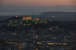 The 5th Century B.C. Parthenon temple is lighted atop the ancient Acropolis hill as in the back ground ferries sale in the Saronic golf, in Athens, on Wednesday, April 10, 2019. (AP Photo/Petros Giannakouris)