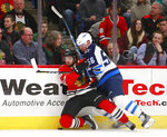 Winnipeg Jets center Marko Dano (56) checks Chicago Blackhawks left wing Vinnie Hinostroza (48) into the boards during the first period of an NHL hockey game Friday, Jan. 12, 2018, in Chicago. (AP Photo/Jeff Haynes)